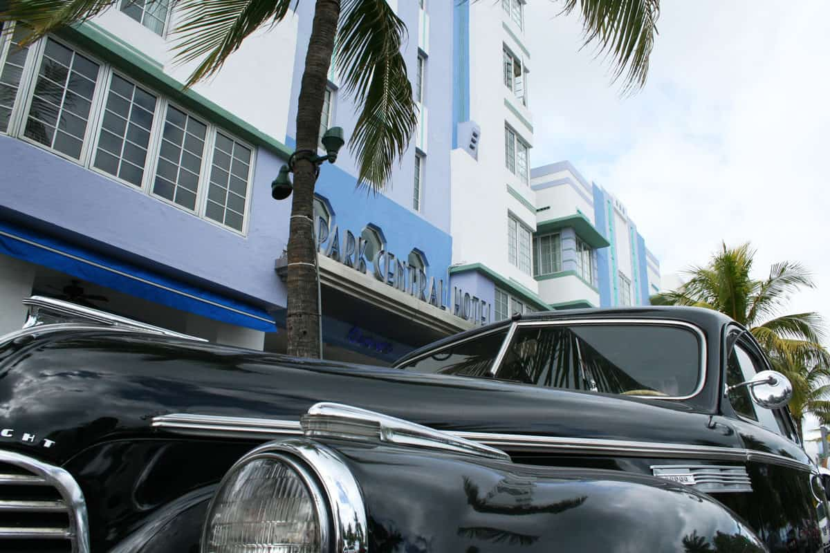 The bonnet of a black classic car with palm trees and one of Miami's iconic art deco hotels in the background. The art deco district in Miami is one of the most popular attractions.