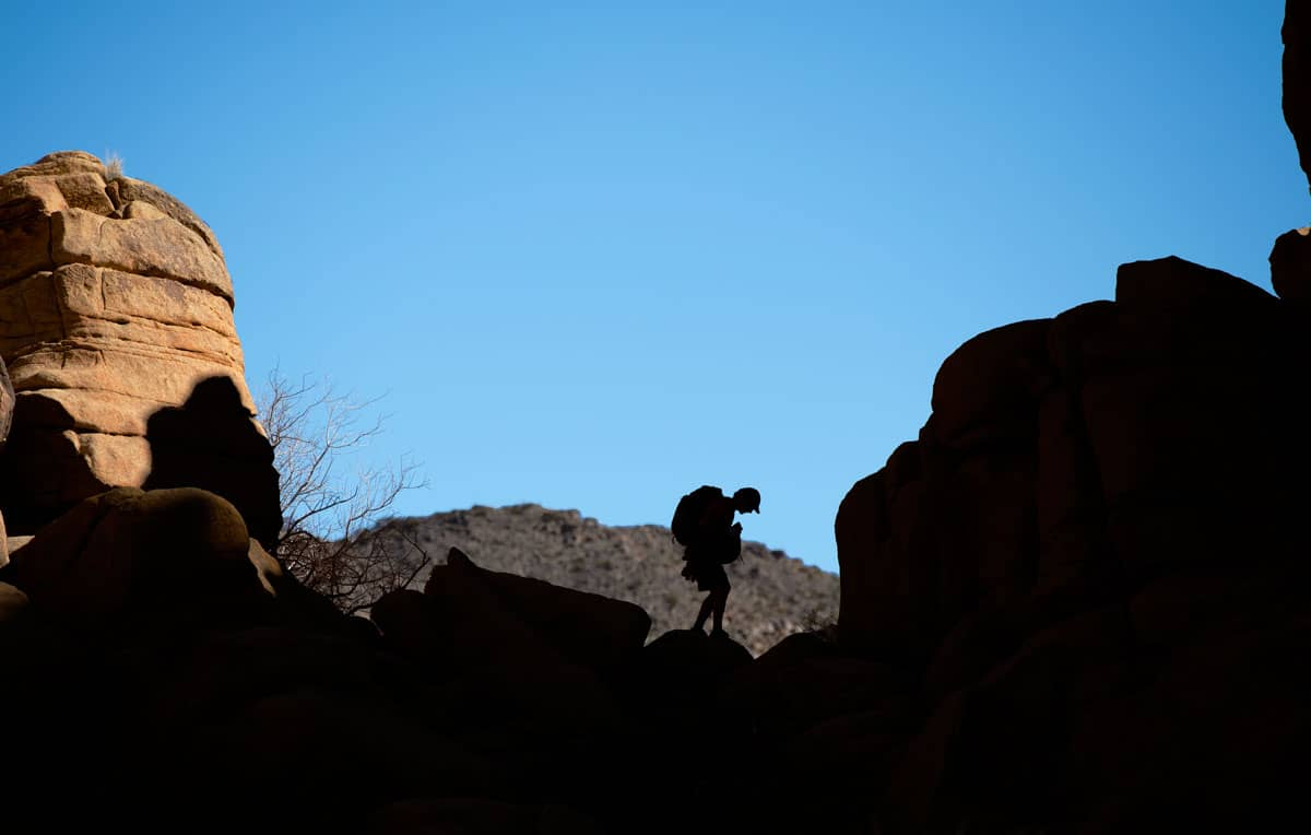 Silhouette of a man hiking through rocks in Joshua Tree National Park