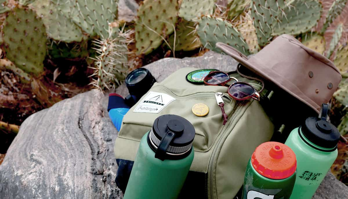 Backpack, Hat, sunglasses and water bottles lying on rocks among cactus. When hiking in Joshua Tree always remember water and sun protection.