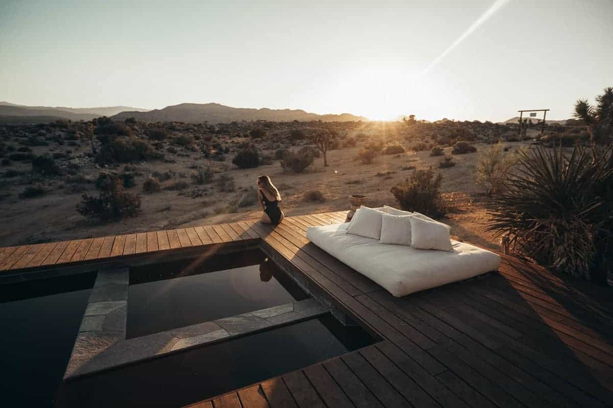 Lady sitting on the edge of a pool overlooking the desert in Joshua Tree USA. There is lots of luxury accommodation in Joshua Tree for those who want to indulge in the desert.