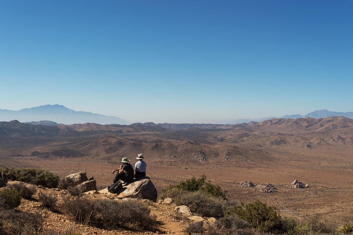 Two people sitting at the top of Ryan Mountain Summit, one of the most popular hikes in Joshua Tree National Park