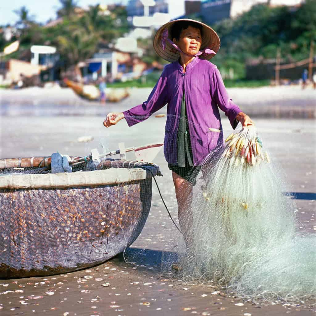 Local fisherwoman standing by a basket fishing boat holding a fishing net on the beach in Mui Ne Vietnam