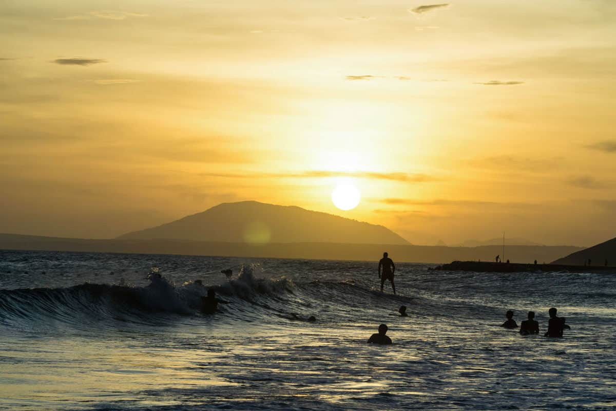 Surfers riding waves at sunset in Mui Ne Vietnam