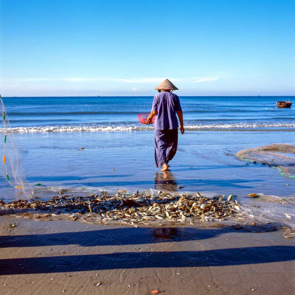 Fisherman standing on the beach with fishing net loaded with fish on the sand .