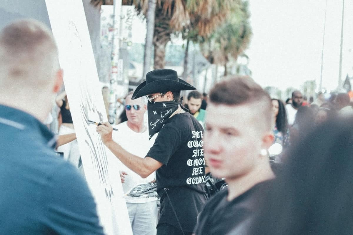 Artist painting among the crowd in the street in Wynwood Miami. The Wynwood Art Walk Block Party is free and happens every second Saturday