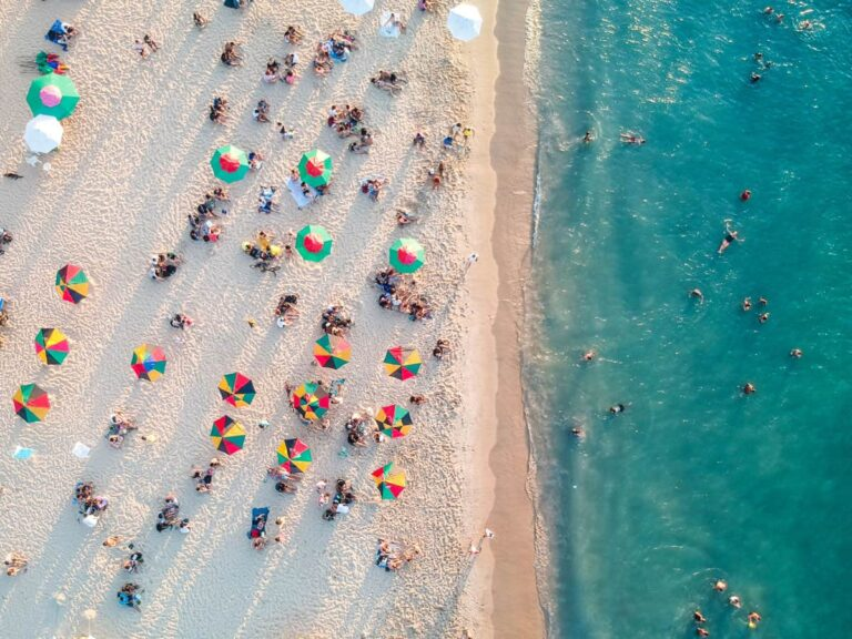 Over head view of Miami beach with the sand and sea, people swimming and colourful beach umbrellas. The beach is one of the best free things to do in Miami.