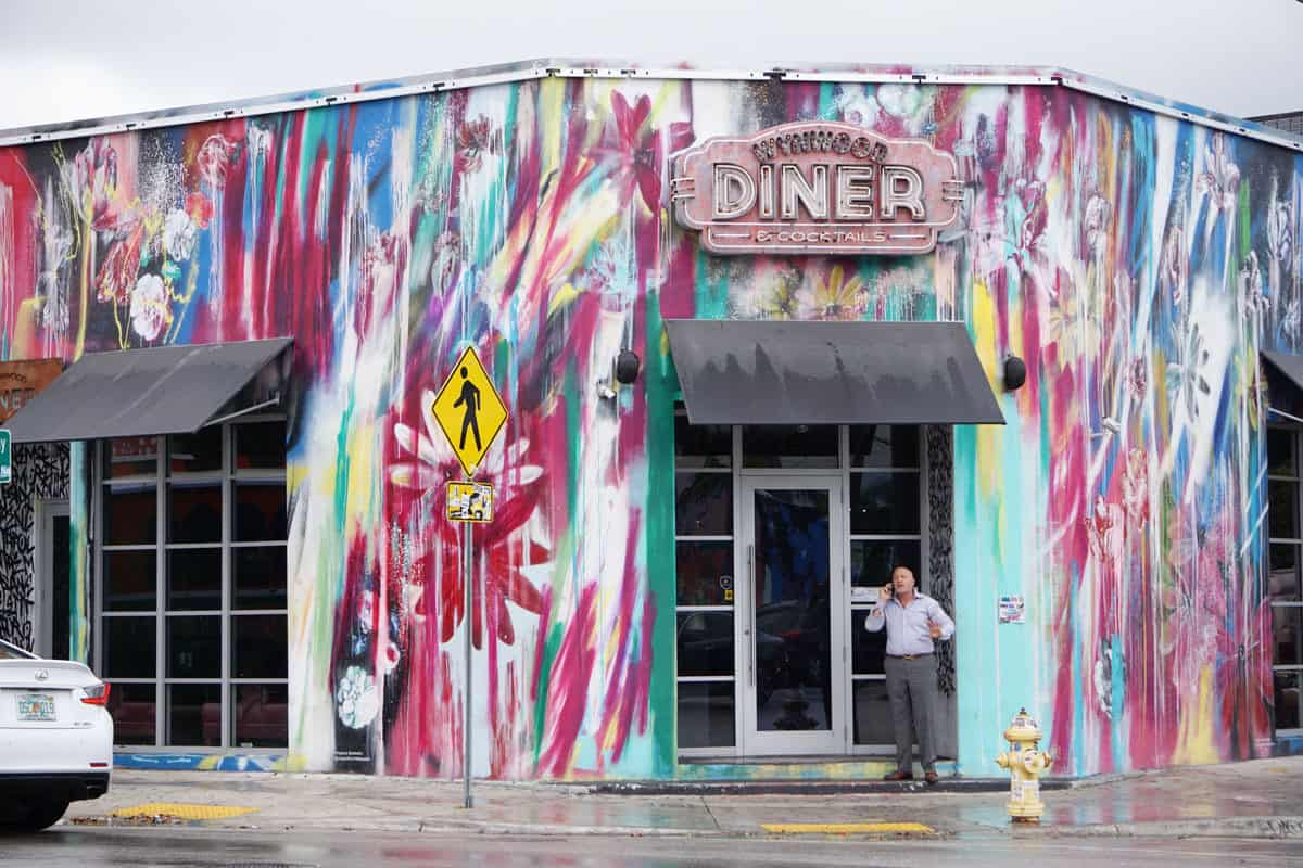 Man standing out the front of a typical american diner brightly painted with murals. The street art of Wynwood Diner.
