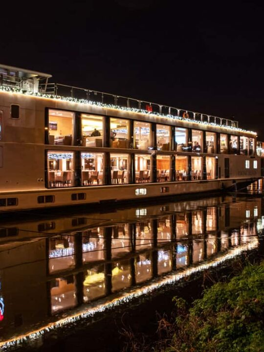 A viking river cruises ship sits docked at night lit up with christmas lights. You can expect beautiful scenes like this on Viking Christmas cruises thanks to the shorter days.