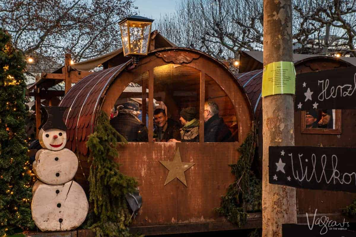 people sit cosily in little wooden chalet nooks enjoying the festive fare offered at Europe's best Christmas markets. These are the kind of experiences you can expect on a Christmas market cruise