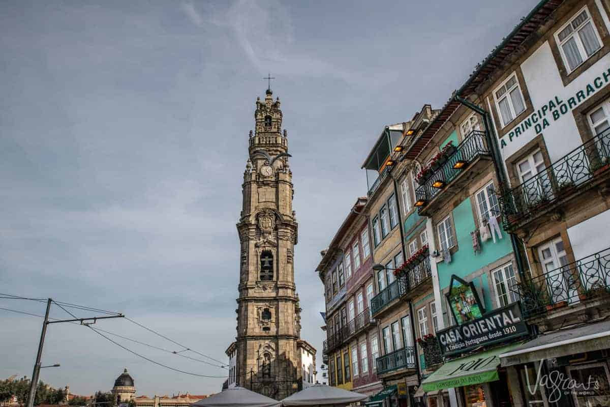 The Torre dos Clérigos on the skyline of Porto with classic colourful buildings framed to the right.