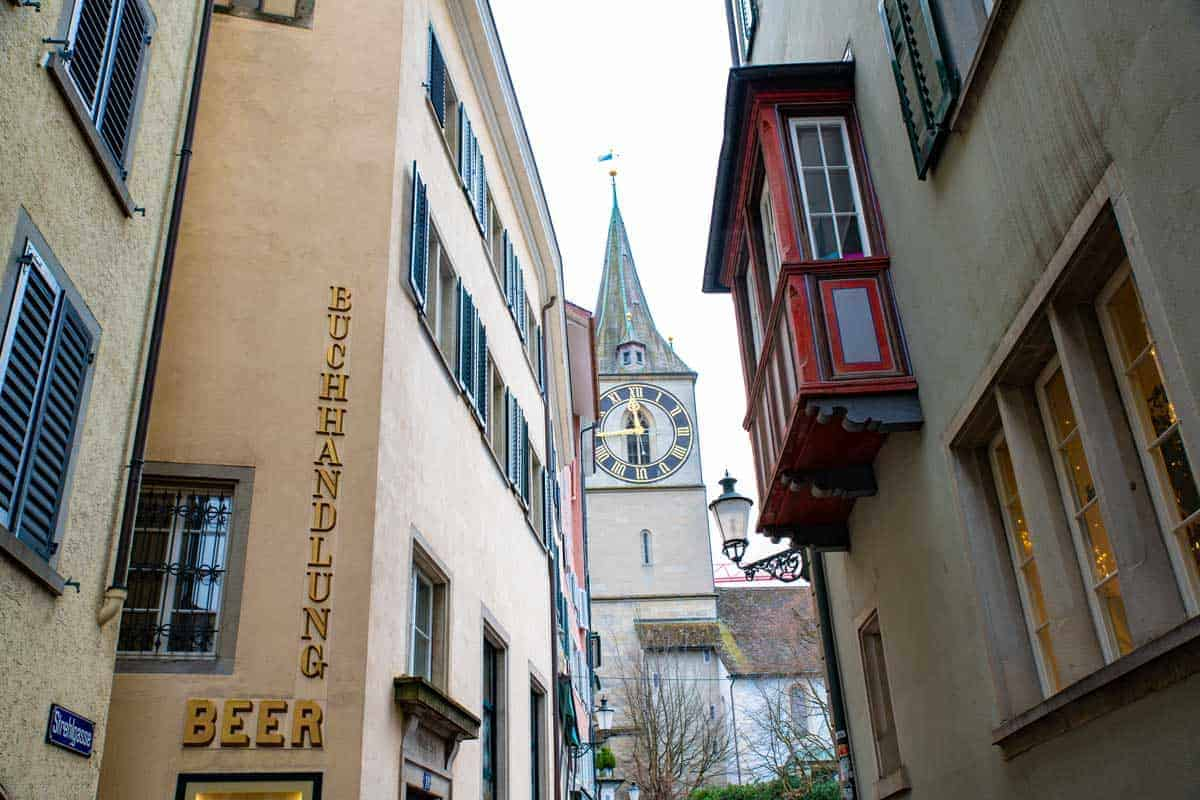Narrow streets of Zurich with the church steeple on the skyline.