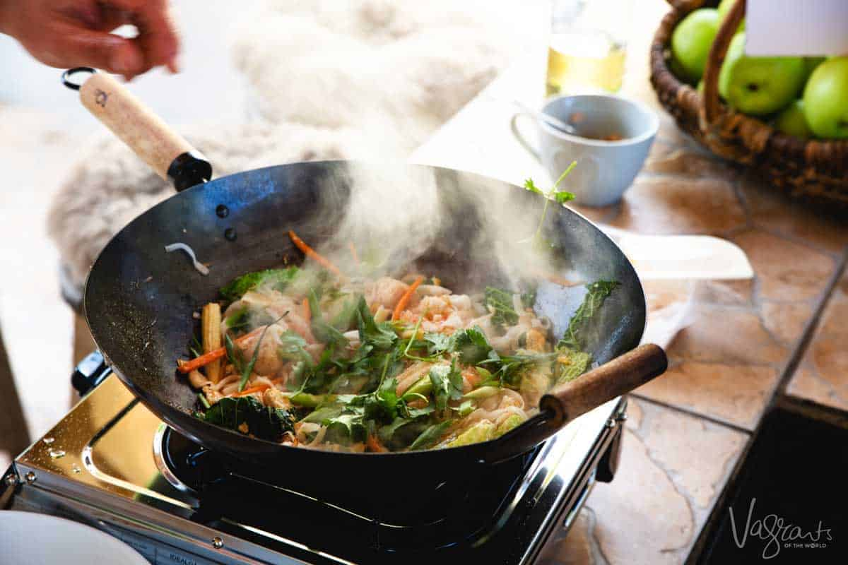 Thai food being cooked quickly in steaming hot wok. A Thain cooking class is a great addition to any any 3 days in Chiang Mai