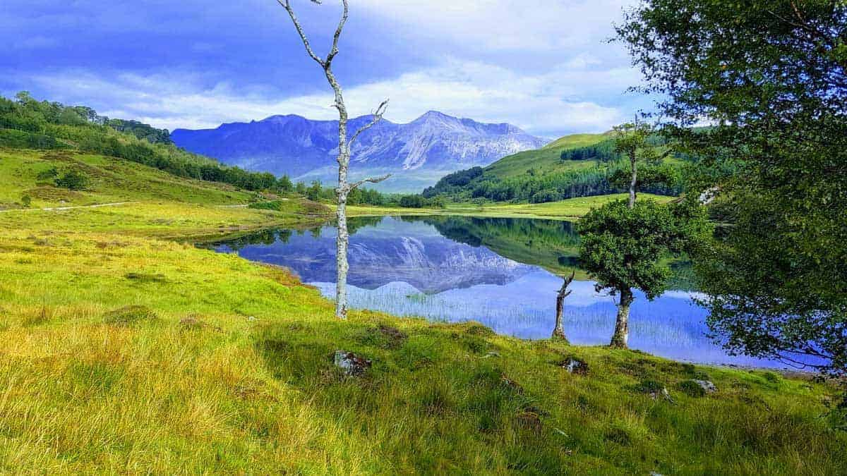 Beinn Eighe, Scotland with lush green grass and snow dusted mountain reflections in the river. Hiking in Scotland, or Hill Walking as it is known, offers hikers beautiful landscapes like these.