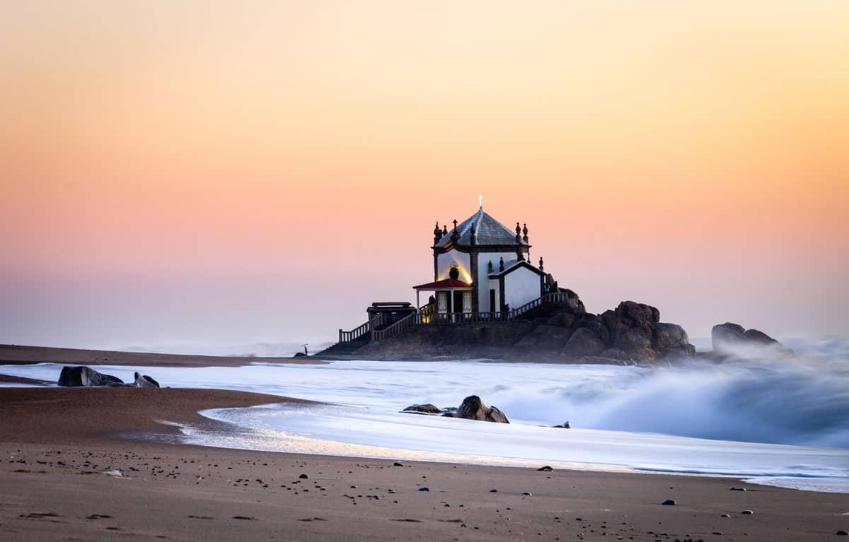 Capela do Senhor da Pedra amongst the waves and red skies.