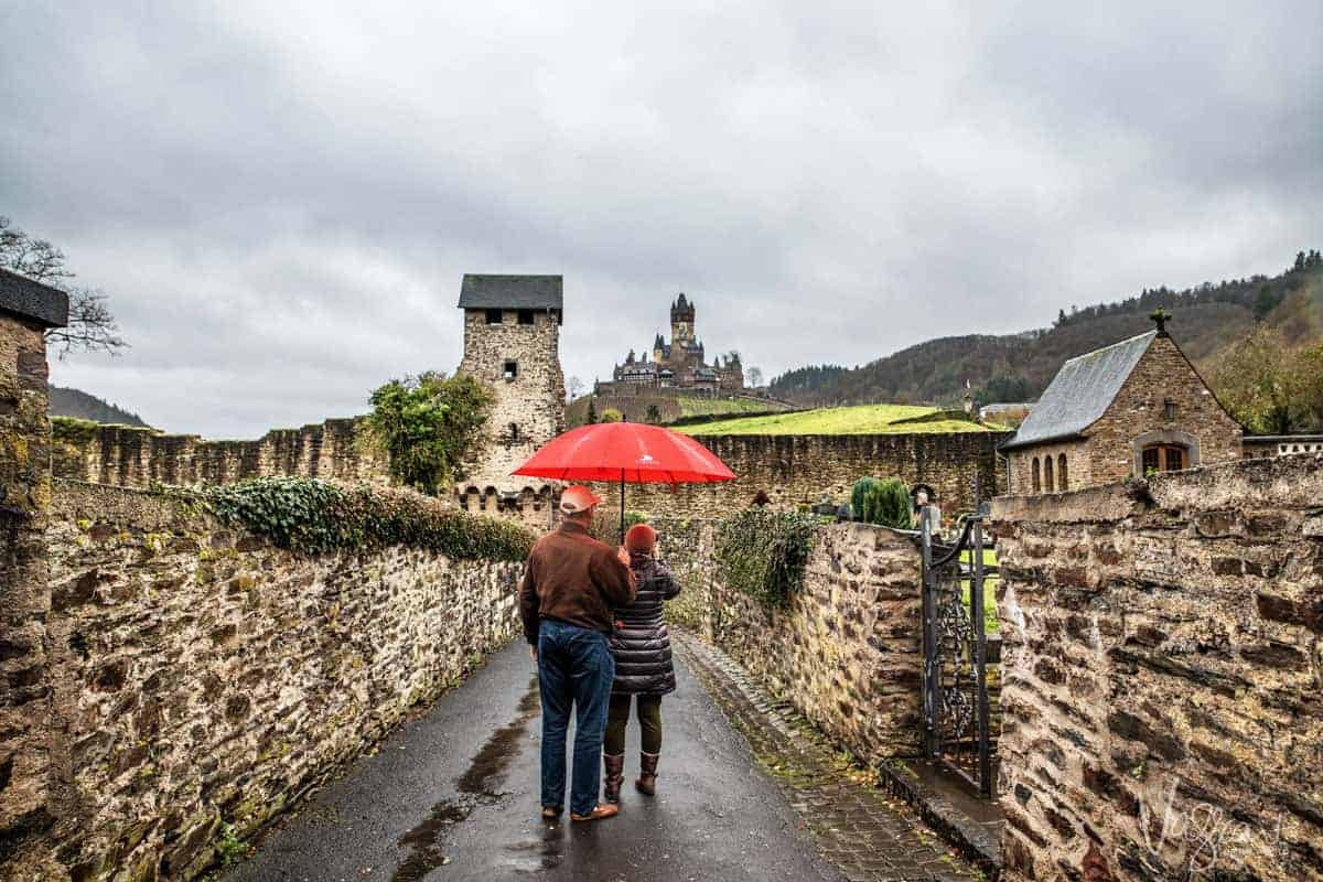 Couple standing under a red umbrella on a country lane surrounded by fields photographing the Reichsburg Castle in Cochem Germany. one of the stops on the Rhine Christmas cruise with Viking Cruises.
