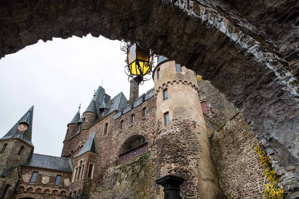 Looking up at Reichsburg Castle through a stone arch. One of the famous fairytale castles to see on the Moselle and Rhine regions of Germany on a Christmas market river cruise.