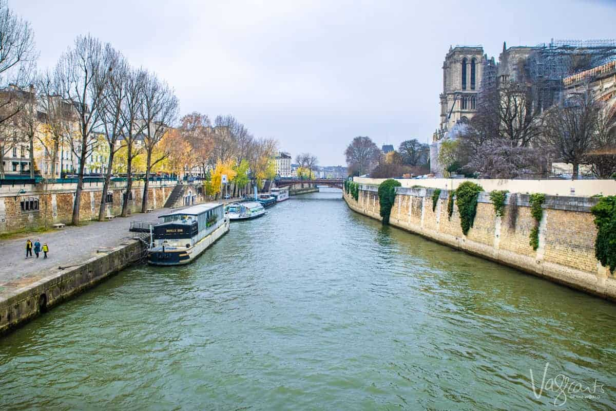 Looking down the Seine in Paris with the canal boats and the Notre Dame Cathedral on the right.