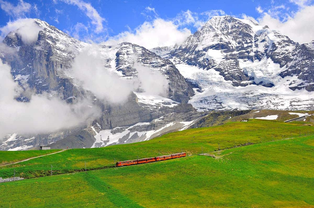 One of Switzerland's biggest attractions is the Jungfraujoch Train crossing a lush green field with the snow covered Swiss Alps in the background.
