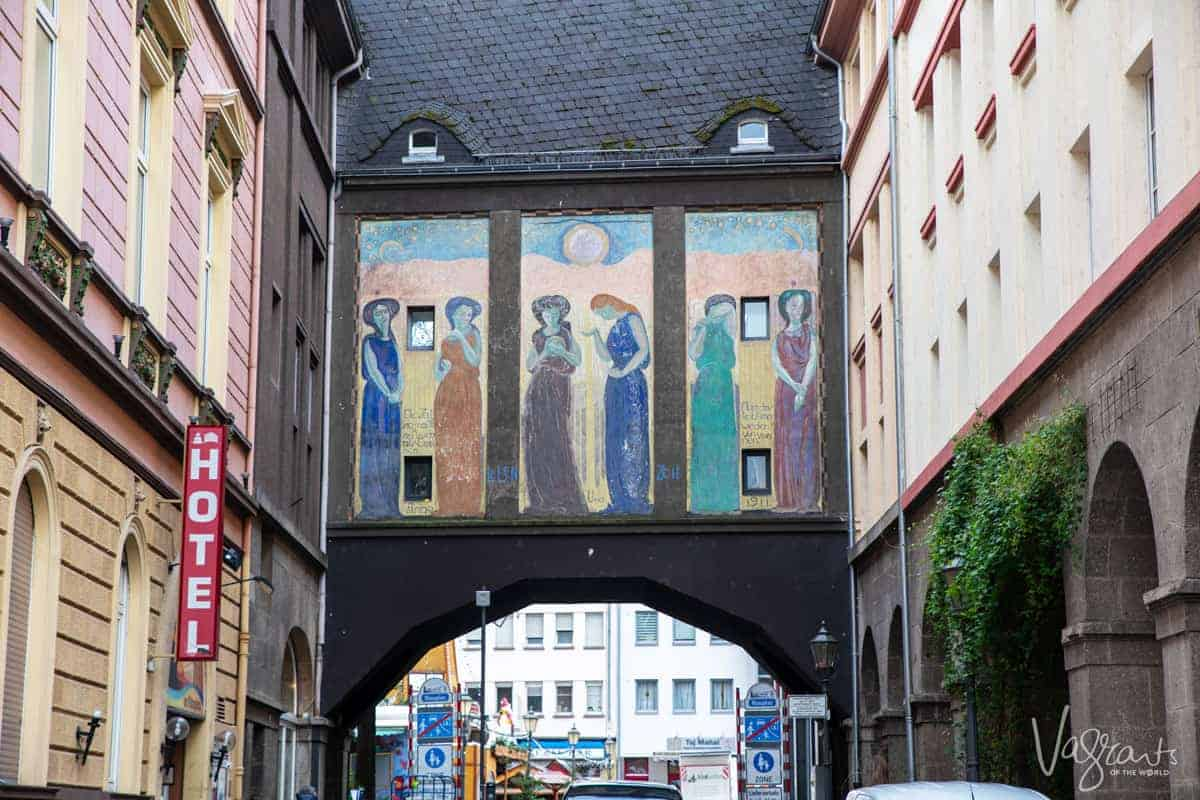Looking at an arch way in the old town with painted panels above the arch depicting women in the old town of Koblenz Germany.