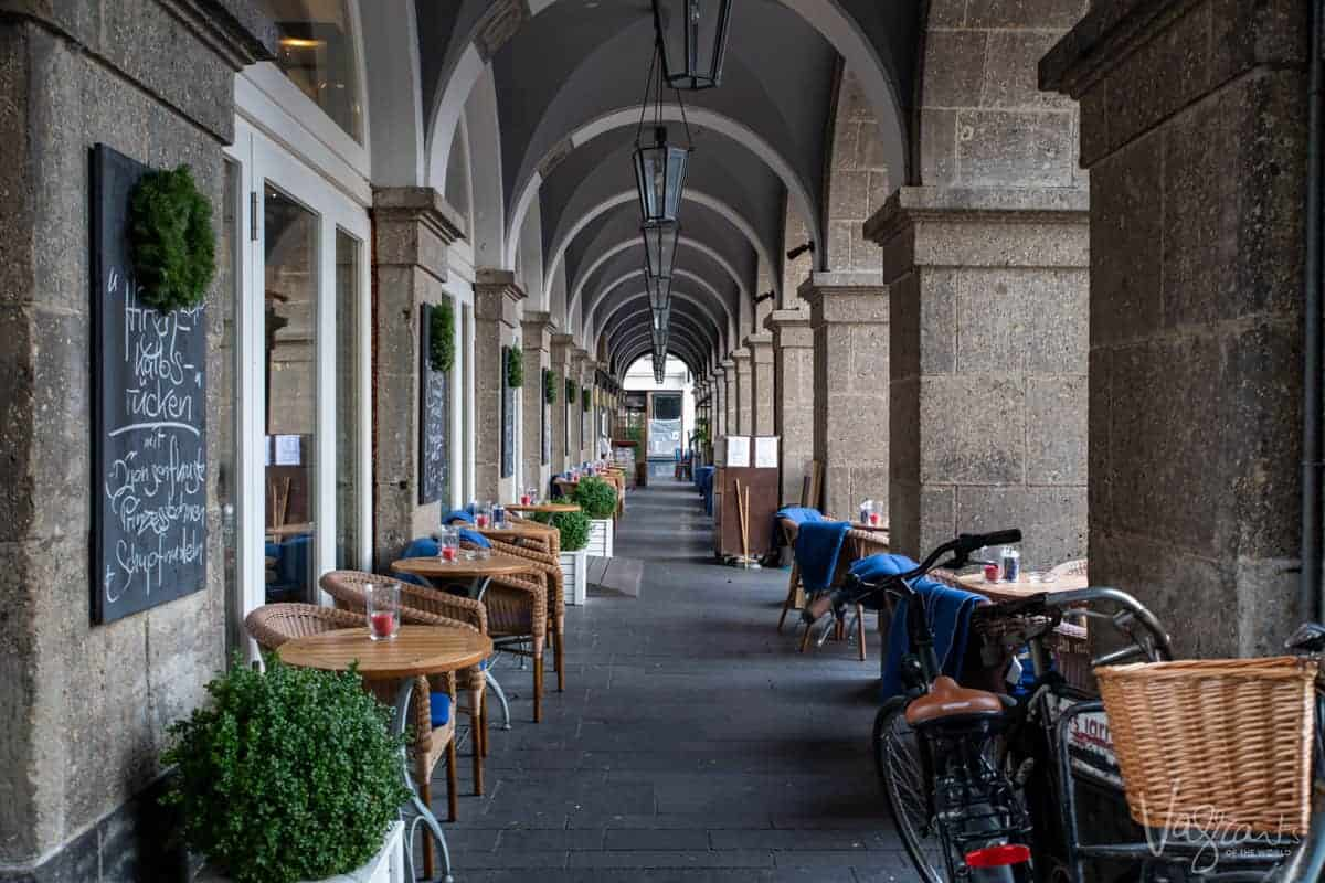 Looking down an arched walkway lined with cafe chairs in the historical centre of Koblenz Germany