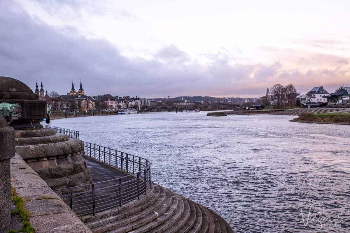 Looking down river at the town of Koblenz in Germany at the confluence of the Rhine and Moselle rivers as the sun rises. The beginning of the scenic sailing on a Rhine river cruise.