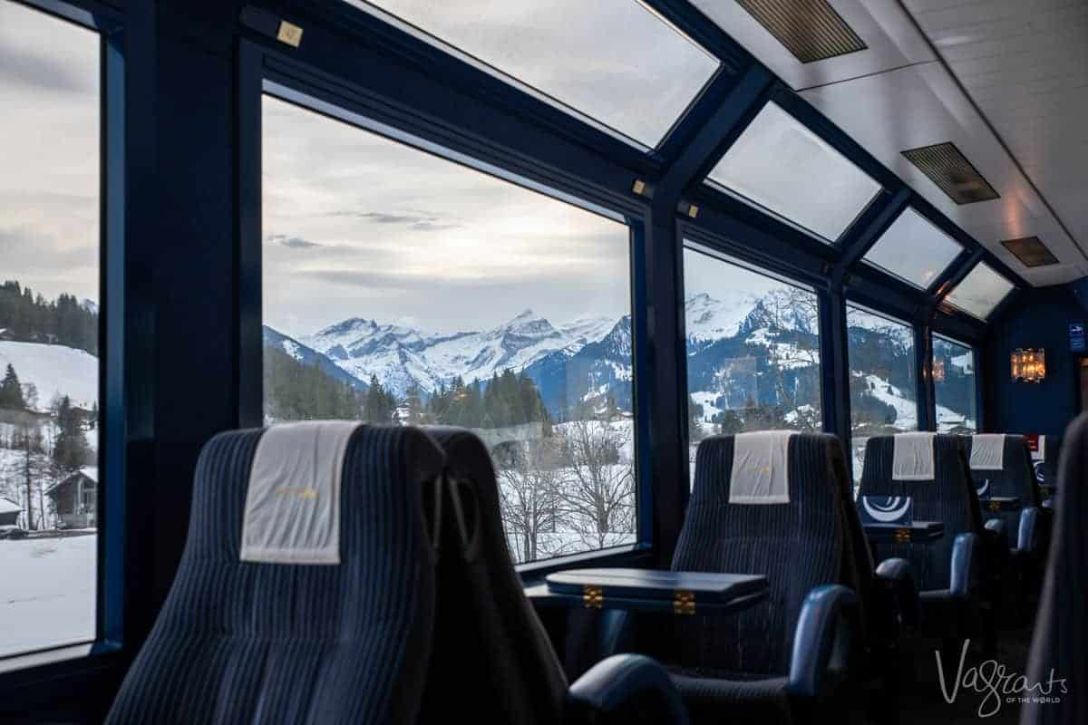 First class train carriage on the Panoramic Golden Pass Train with the snowy Swiss Alps on the horizon.
