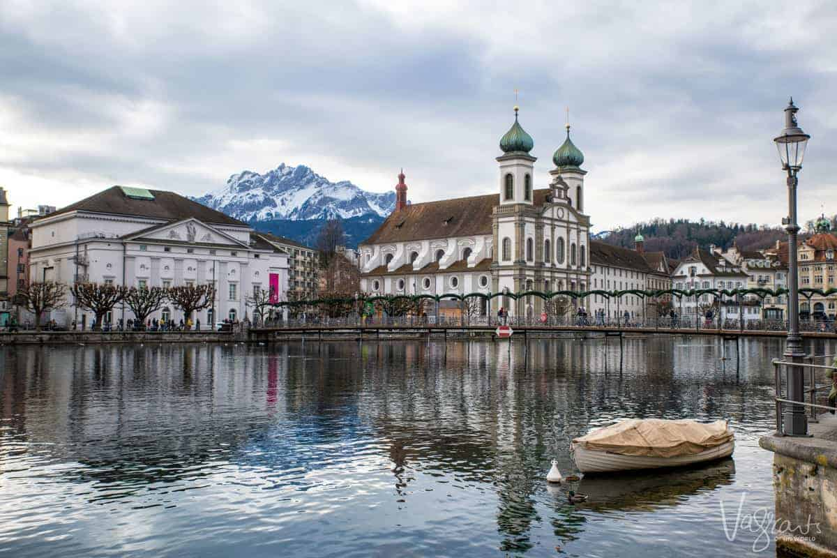 Old city of Lucerne over the river with the Swiss Alps in the background.
