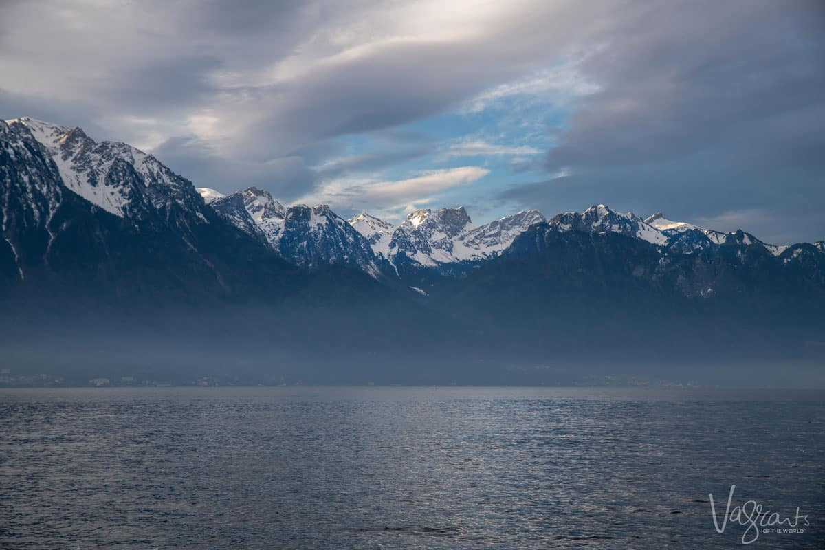 Lake Geneva with mist on the water and the sun breaking through the clouds over the Swiss Alps