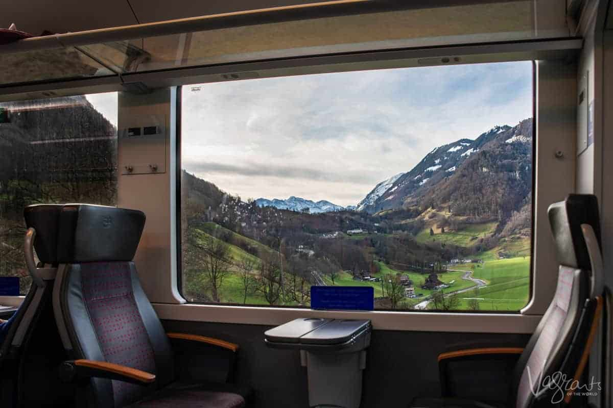 Luxury seats next to the train window and lush green Swiss countryside and the Swiss Alps between Interlaken Ost and Zweisimmen on the Interlaken Express, Golden Pass Line.