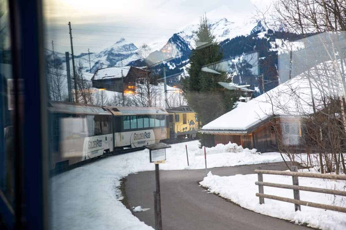 Train window view on a bend towards the front of the panoramic train on the Golden Pass line as it passes through a snowy alpine village in the Swiss Alps