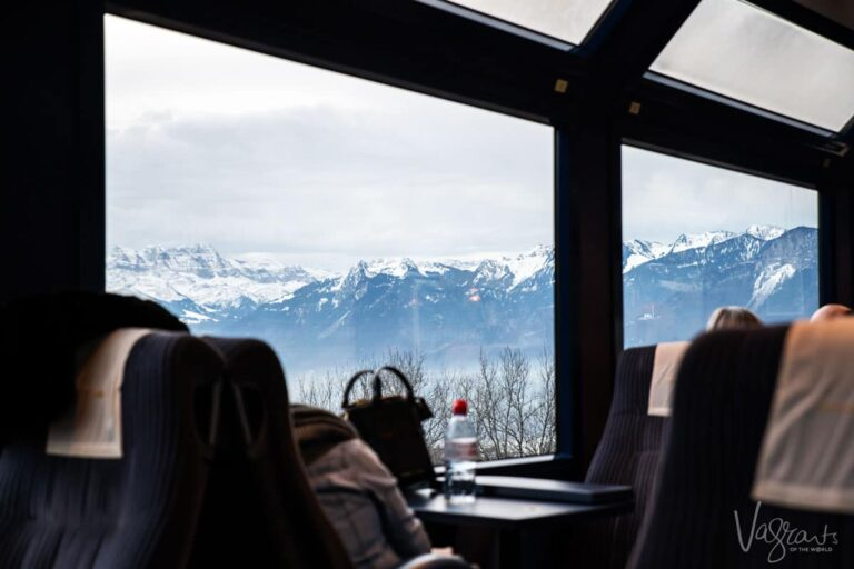 Looking across the train at the seats by the panoramic windows on the Golden Pass Train with views of the magnificent Swiss Alps. These are the types of scenes you can expect taking the train from Lucerne to Montreux