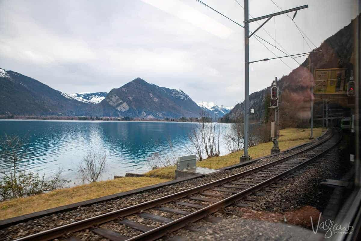 Reflection of a man in the window of a train looking out over a crystal blue lake in Switzerland travelling on the Golden Pass Railway