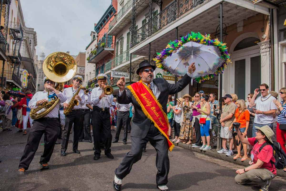 Brass band with band leader holding a colourful umbrella at the New Orleans French Quarter Festival