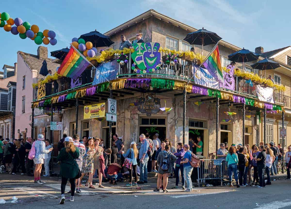 People standing outside a typical bbar in the French Qaurter of New Orleans during Mardi Gras festival