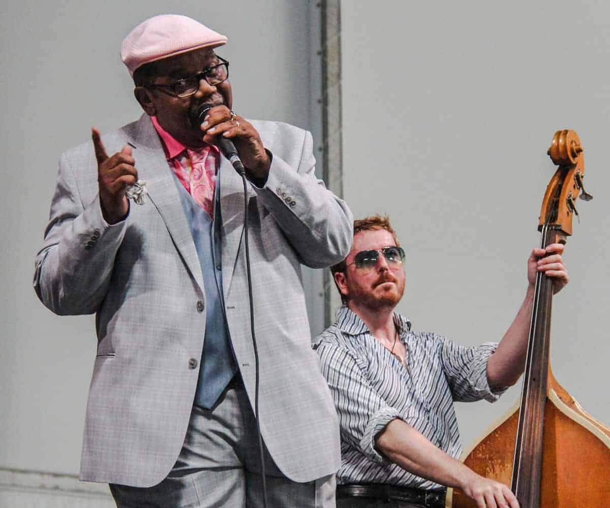 Black man in a suit and hat sinnging jazz with a bass player sitting behind at the Satchmo summerfest in New Orleans
