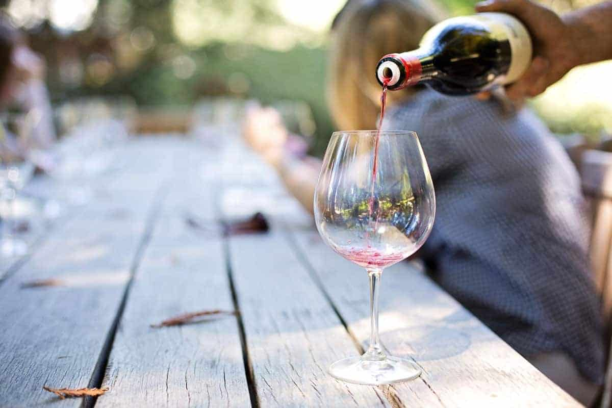 Glass of wine being poured on a wooden table outside at the New Orleans food and wine event