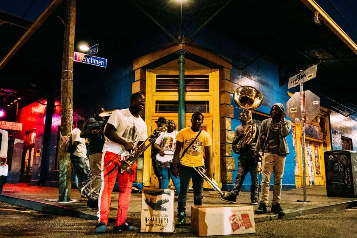 A group of buskers standing in front of brightly coloured houses on Frenchman street New Orleans
