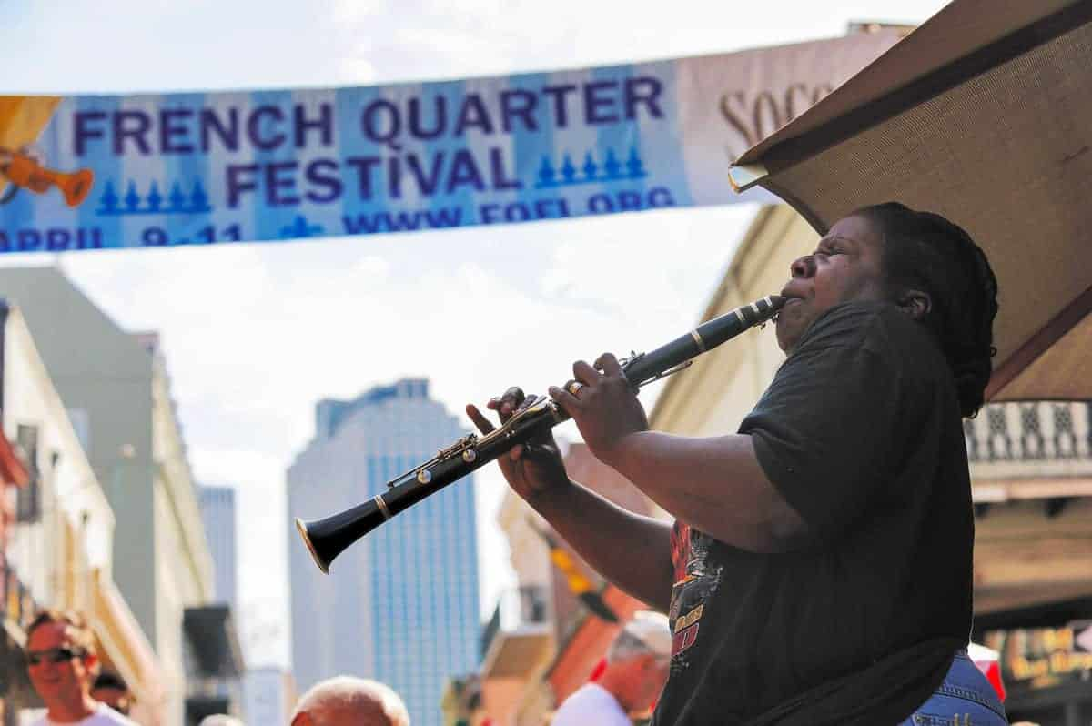 Person playing clarinet with New Orleans French Quarter festival banner in the background