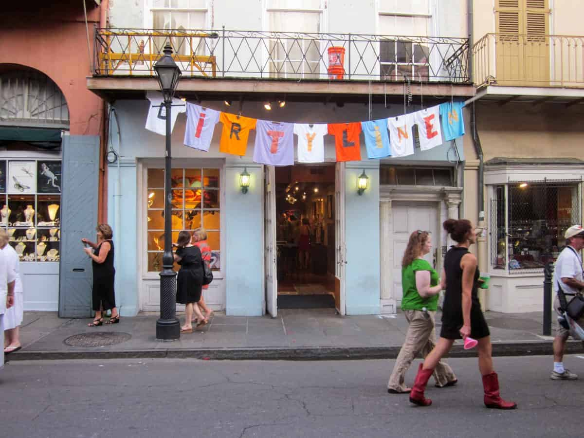 People walking down the street in front of a shop with a Dirty Linen banner out front. Part of the Dirty Linen festival in New Orleans.