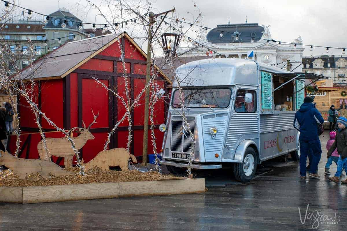 Zurich Christmas markets. A silver food van parked in front of bright red Christmas huts.