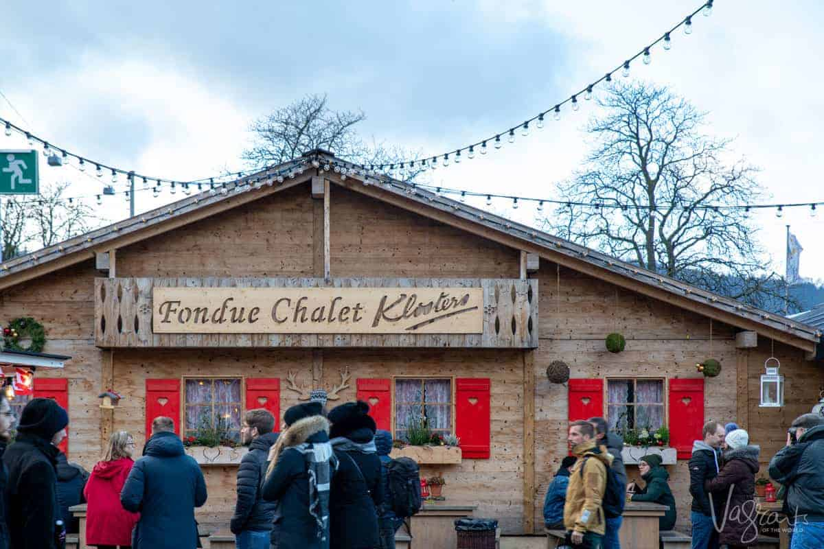 people walking in front of a wooden building - Fondue Chalet at the Zurich Christmas Markets