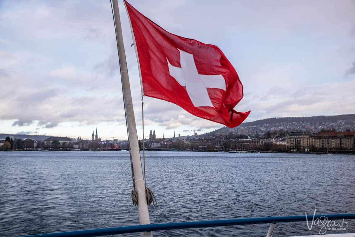 View of the Swiss flag from the back of a ferr looking back at Zurich city
