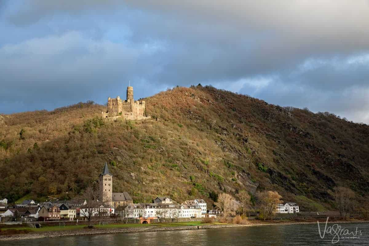 View of a picturesque town on the Rhine river with a castle on the hill above. Just one of the scenes you can expect on a Rhine river cruise.