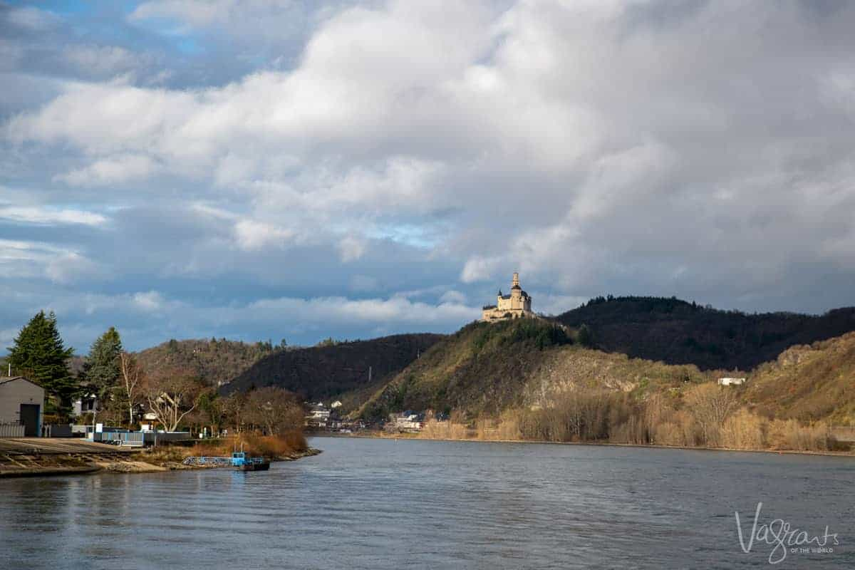 Looking down river on a Rhine river cruise with a castle on the hill in the distance.