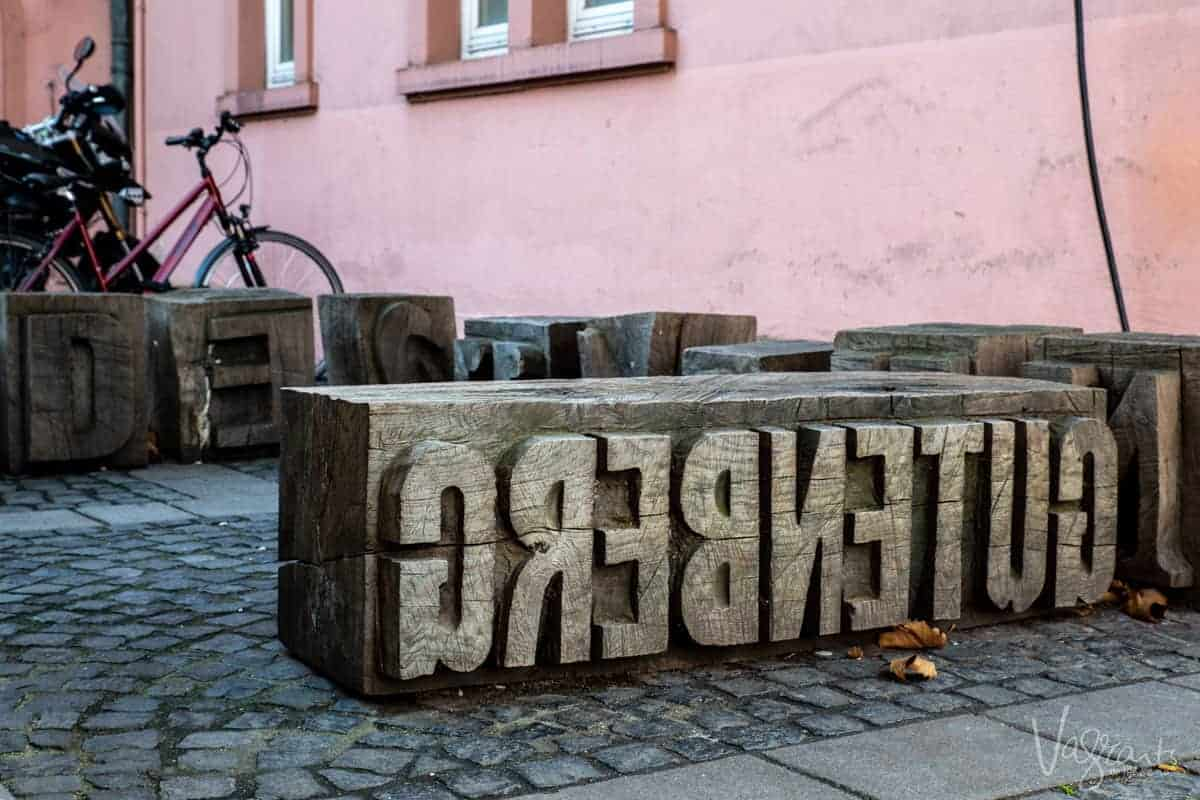 Carved timber sign that reads Gutenberg backwards in the style of the printing press he invented. The Gutenberg museum is one of the stops on a Rhine river cruise.
