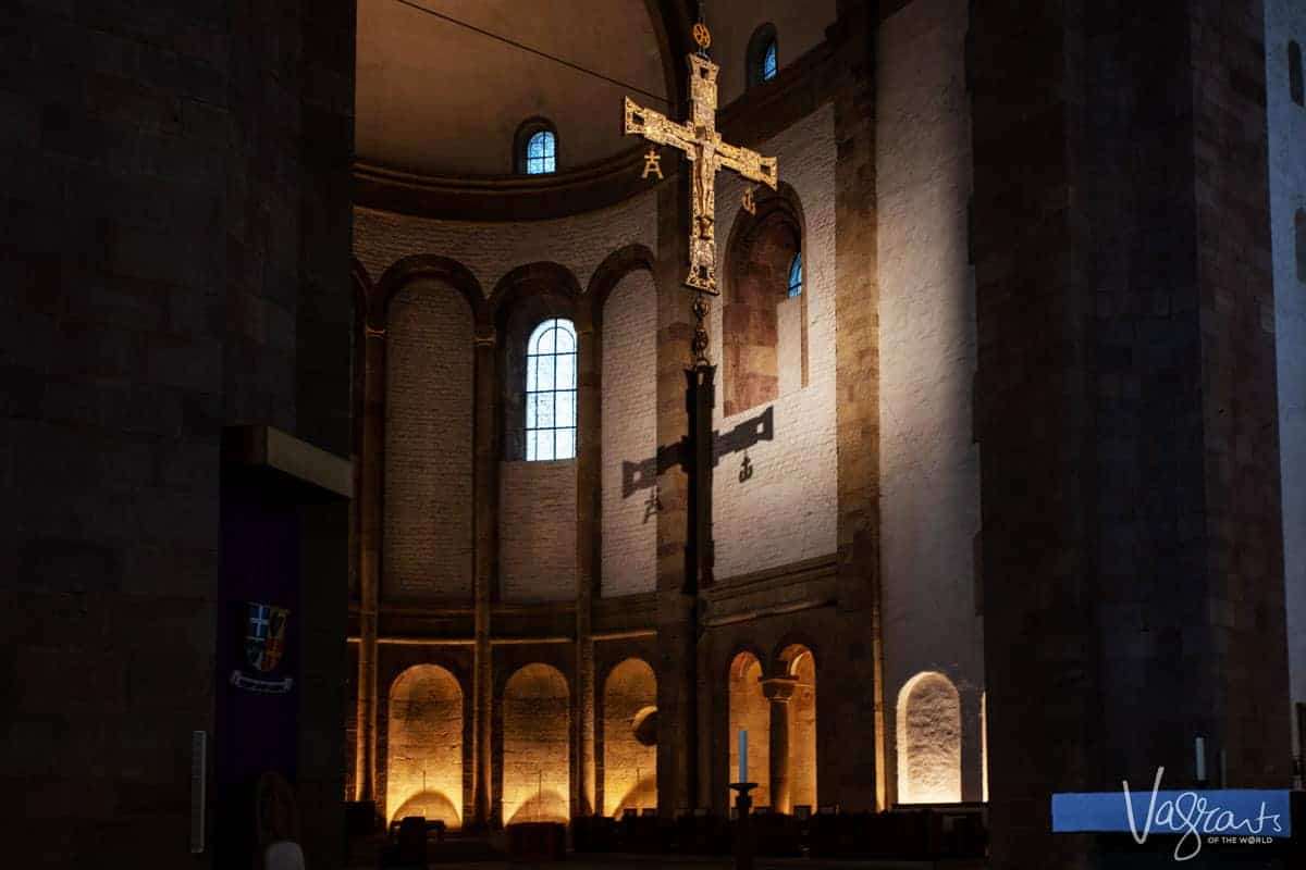 Interior of Speyer cathedral in Speyer Germany. looking up at the main cross over the alter with the shadow of the cross on the back wall with lit alcoves.