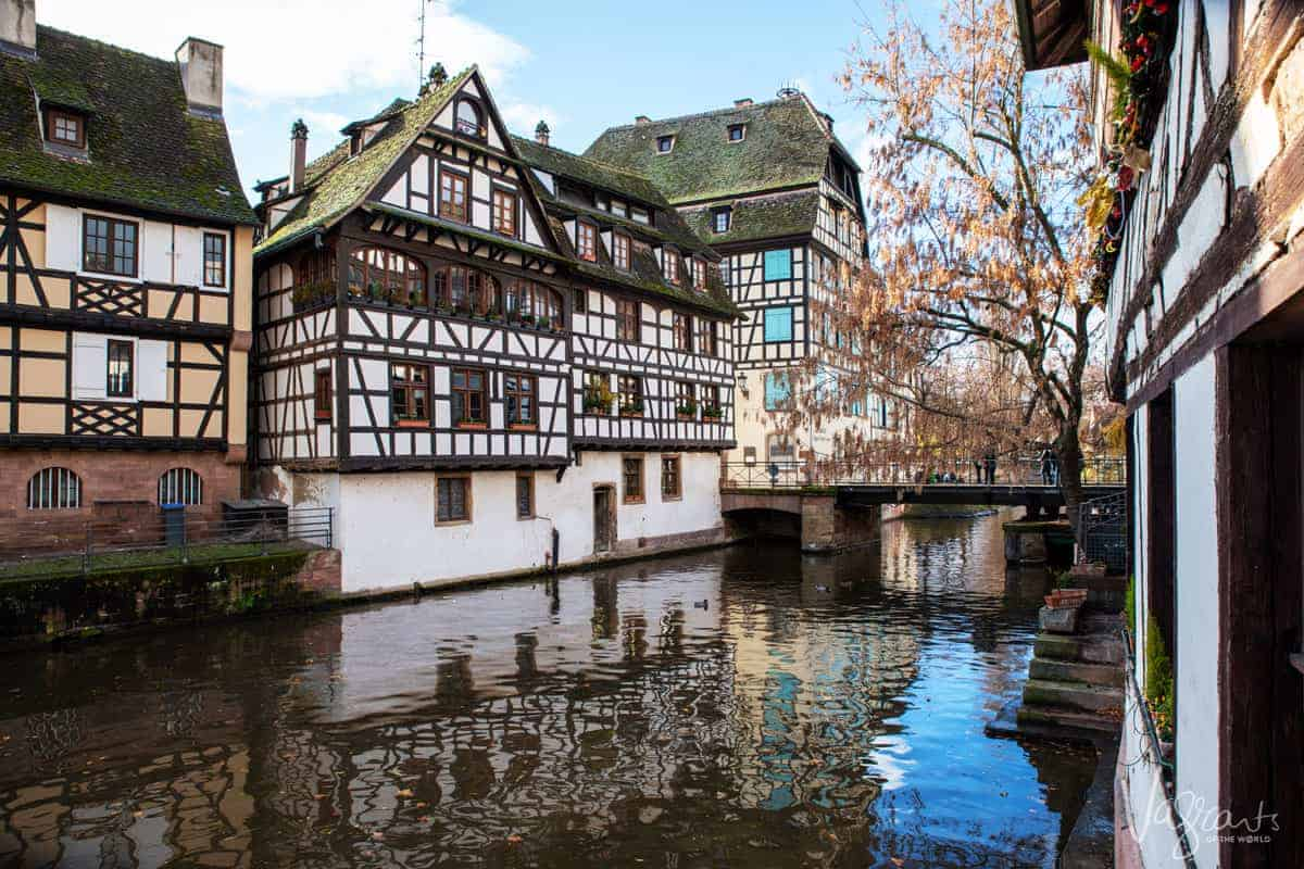 Looking over the canals at the brightly coloured wooden houses reflecting in the water in Strasbourg France. One of the best stops on the Rhine river cruise for the best Christmas markets in Europe.