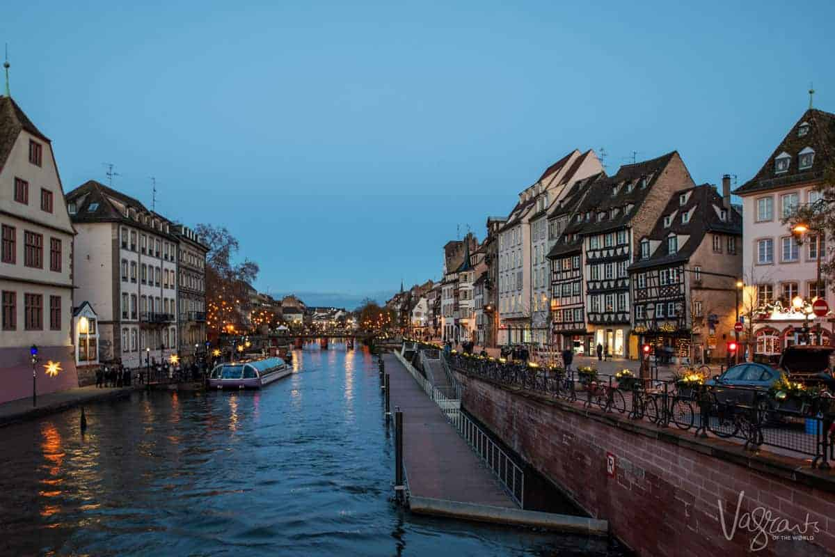 Looking down the canals in Strasbourg France at night with the buildings brightly lit either side