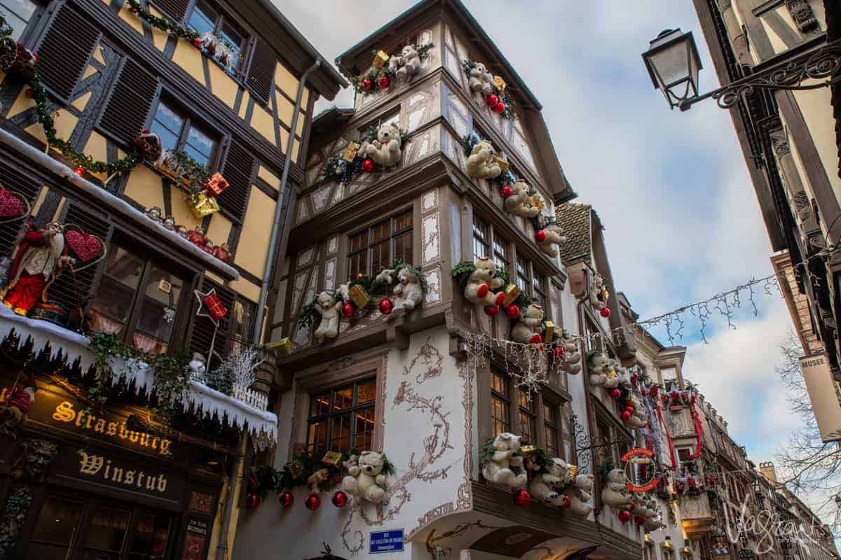Looking up at the timber houses in Strasbourg old town covered with Christmas decorations and giant Christmas teddy bears.