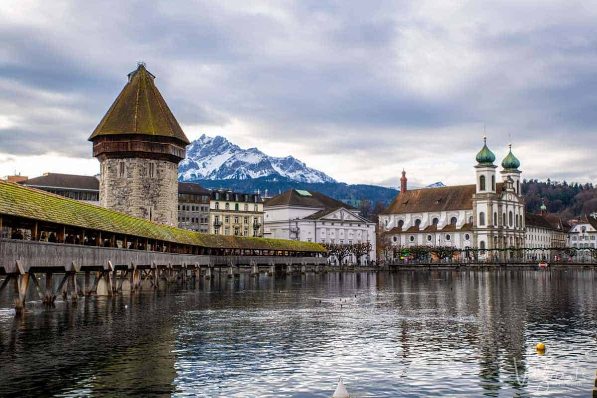 Lucerne Old Town with the covered wooden bridge and tower in the foreground and the Swiss Alps on the skyline.